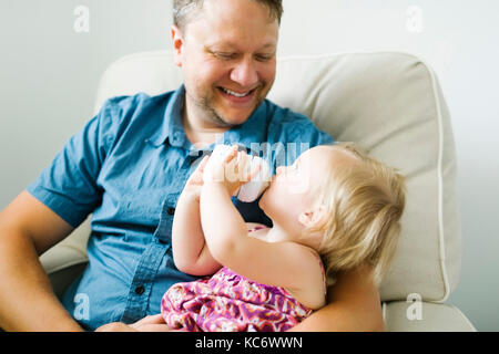 Father feeding baby girl (12-17 months) in living room - Stock Photo