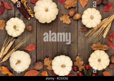 Autumn frame with leaves and white pumpkins over an aged rustic wood background - Stock Photo