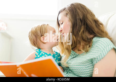 Mother with baby girl (12-17 months) sitting in living room and reading book - Stock Photo