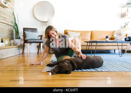 Woman stroking Labrador Retriever in living room - Stock Photo