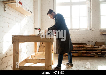 Joiner using electric tools while working in carpentry. Millennial worker getting on-the-job trailing in woodworking - Stock Photo