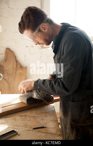 Skilled professional carpenter in workwear and protective eyewear sanding wooden plank, using electric belt sander, - Stock Photo