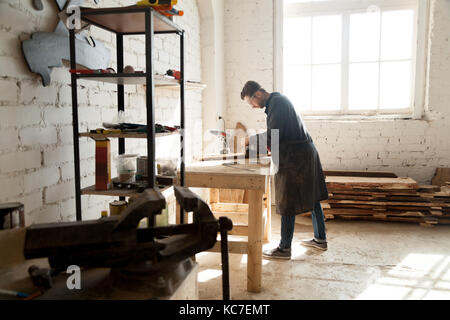 Side view of professional young joiner woodworking in planing shop garage. Skilled craftsman working on customized - Stock Photo