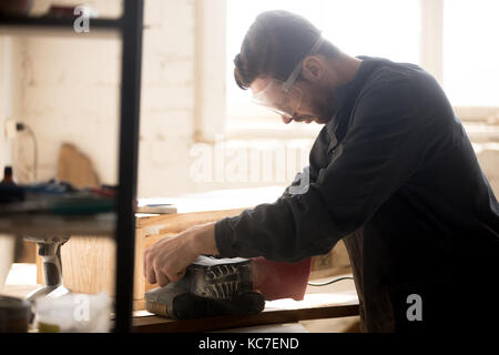 Side view of young joiner wearing protective glasses for safety sanding planks, skilled workman carpenter woodworking - Stock Photo