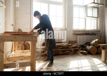 Finish trim carpenter wearing protective clothes and eyewear holding electric power saw, working with wood in workshop - Stock Photo