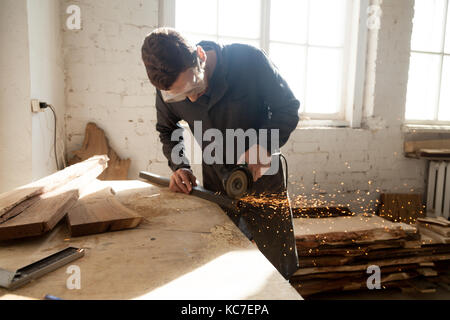 Craftsman in protective glasses cutting steel plank on workbench with angle grinder in workshop. Cabinet maker working - Stock Photo