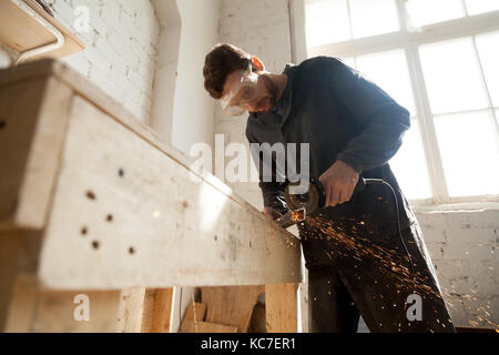Worker in protective eyewear working in small workshop interior using die angle grinder for cutting steel bar, throwing - Stock Photo