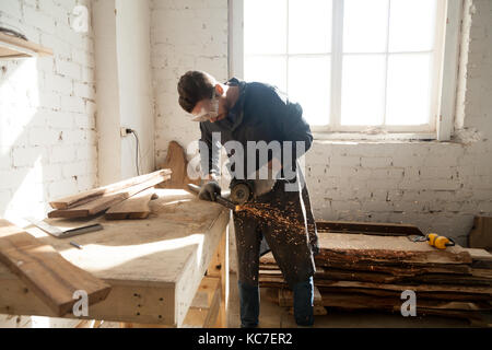 Man starting own small business in home workshop - Stock Photo