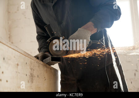 Close up of cutting metal pipe, man using angle grinder - Stock Photo