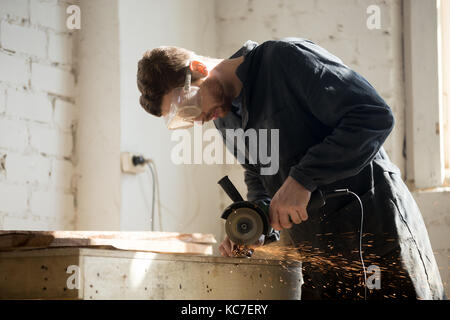 Side view of worker using angle grinder for metal cutting  - Stock Photo