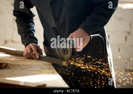 Craftsman working with electric tool in workshop - Stock Photo