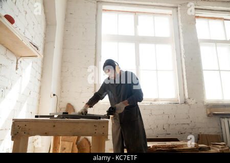 Carpenter works in custom furniture manufacturing - Stock Photo