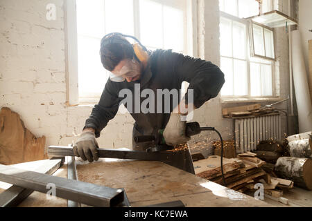 Young workman grinding steel metal profile pipe in workshop inte - Stock Photo