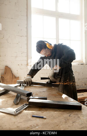 Craftsman making his new project in workshop - Stock Photo