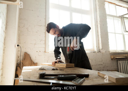 Young carpenter doing woodwork in carpentry - Stock Photo