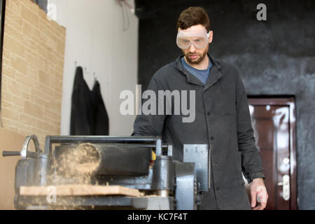 Carpenter in safety glasses works on machine tool - Stock Photo
