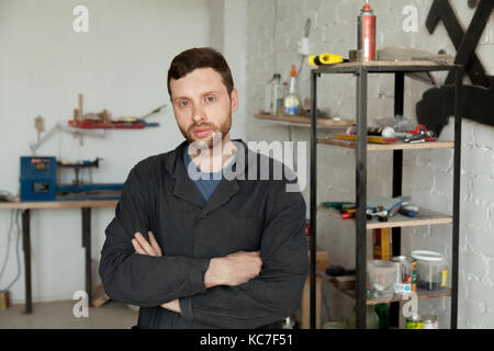 Portrait of serious young handyman standing in own workshop inte - Stock Photo
