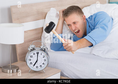 Young Man Smashing Alarm Clock With Hammer On Bed - Stock Photo