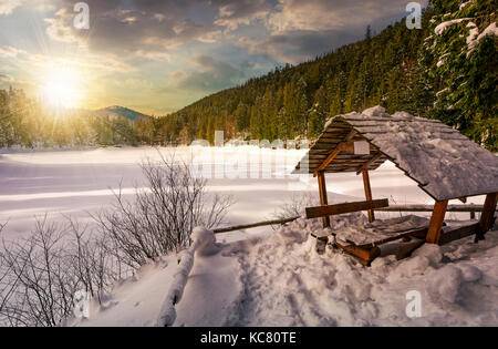 wooden bower in snowy winter spruce forest. beautiful mountainous landscape near snow covered frozen lake at sunset - Stock Photo