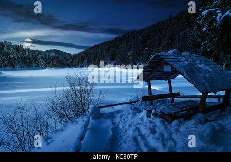 wooden bower in snowy winter spruce forest. beautiful mountainous landscape near snow covered frozen lake at night - Stock Photo