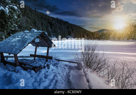 day and night time change concept in winter spruce forest with wooden bower. beautiful mountainous landscape near - Stock Photo