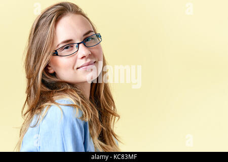Beautiful teenager girl with ginger hair and freckles wearing reading glasses, smiling teen portrait on yellow background - Stock Photo