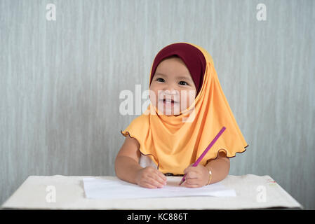asian toddler / baby girl wearing hijab is having fun learning to use pencils while looking at empty space. Education - Stock Photo