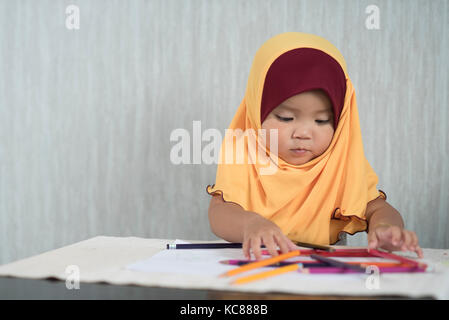 asian little toddler / baby girl wearing hijab is having fun learning to use pencils. Education concept. human growth - Stock Photo