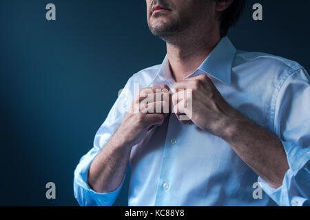 Businessman getting dressed for job interview, man buttoning white shirt - Stock Photo
