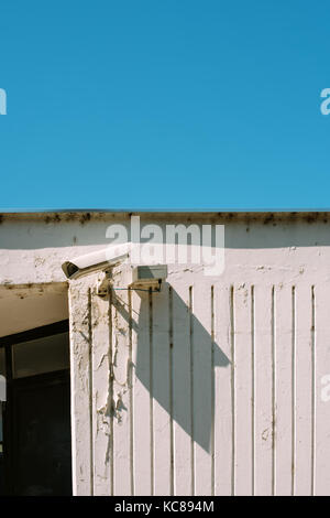 Schoolyard CCTV closed circuit camera for protection and surveillance with blue sky as blank copy space - Stock Photo