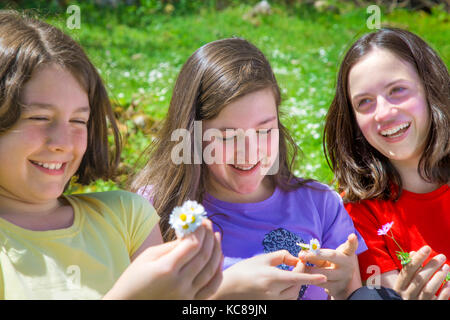 Three beautiful teenage girls laughing and having a good time outdoors at the mountain - Stock Photo