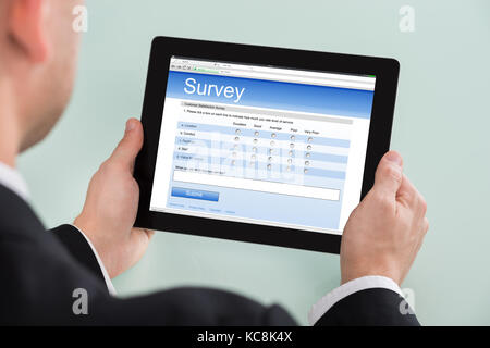 Close-up Of Businessman Looking At Online Survey Form On Digital Tablet - Stock Photo