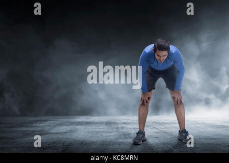 Young asian runner man taking rest from jogging on the concrete floor - Stock Photo