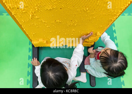 Asian Chinese little girls playing pin board at indoor playground - Stock Photo
