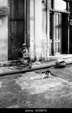 Adult Cuban male sits on doorstep of urban house a cat walks by in foreground. Black and white documentary street - Stock Photo