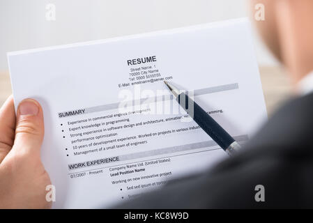close up of a businessman analyzing resume at desk in office stock
