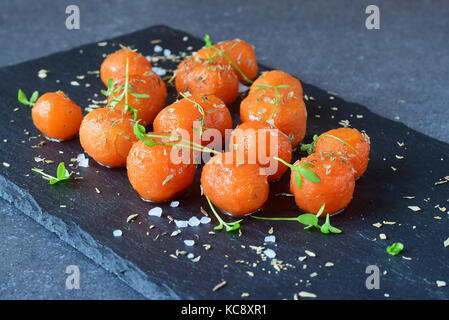 Honey glazed baby carrots with sea salt and thyme on a grey abstract background. Healthy eating concept. Fastening - Stock Photo