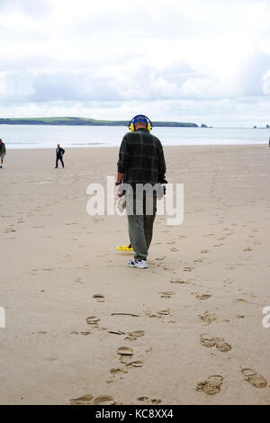 Man using a metal detector on Tenby beach,Penbrokeshire,South Wales, UK. - Stock Photo