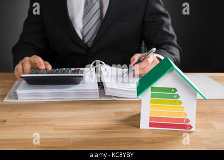 Businessman Calculating Financial Data With House Model Showing Energy Efficiency Rate On Desk - Stock Photo