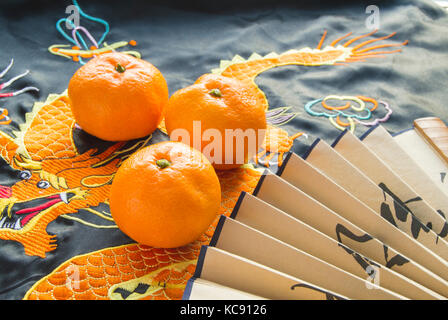 Chinese New year, tangerines and a fan lying on the silk fabric with an embroidered dragon. - Stock Photo