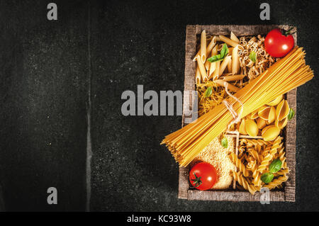 Selection of various raw italian pasta with basil leaves and cherry tomato, in old wooden box on dark stone table, - Stock Photo