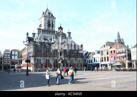Young tourist girls in front of 17th century Renaissance style City Hall (Stadhuis) on the central Markt square - Stock Photo