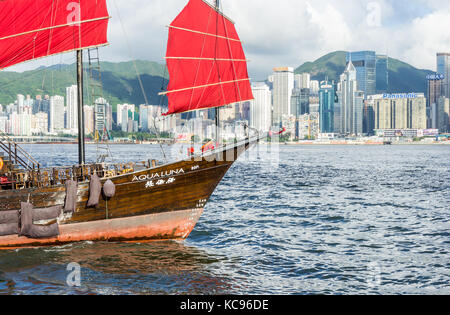 Iconic Aqualuna ship with bright red sails in Victoria Harbor in Hong Kong SAR - Stock Photo