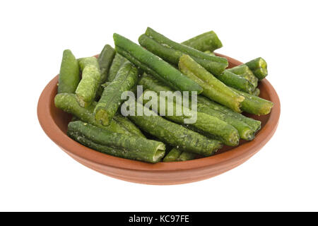 A small bowl filled with dried and salted green beans isolated on a white background. - Stock Photo