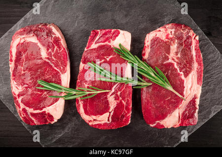 A closeup of three slices of raw meat, beef fillet, shot from above on black textures with sprigs of rosemary and - Stock Photo