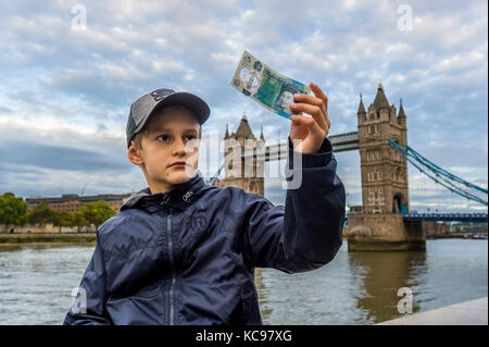 boy in baseball cap holding and looking at new british 5 pound banknote - Stock Photo