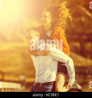 Happy man carrying his girlfriend on the back on on the bridge over the river. Vintage tone - Stock Photo