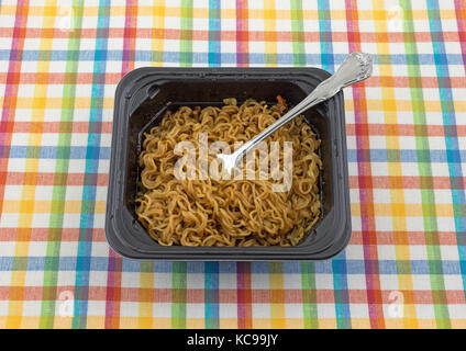 A serving of beef flavored ramen noodles with a fork in a black microwavable tray atop a colorful place mat. - Stock Photo
