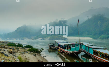 Slow Boat Docked on the bank of the Mekong - Early Morning, Loas, Asia - Stock Photo