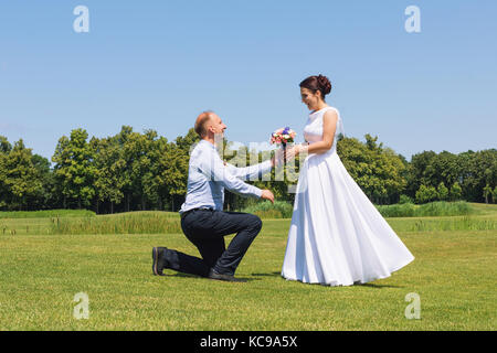 Man makes a proposal to his girlfriend to get married. Marriage proposal. Love and marriage concept. Young attractive - Stock Photo